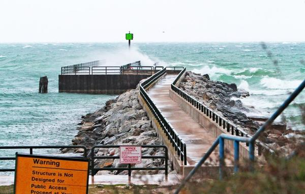 Waves break over the break wall on the north side of the Pine River Channel on Tuesday in Charlevoix thanks to recent winds from Hurricane Sandy.