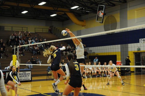 Petoskey senior Megan Tompkins (right) blocks an attack from Gaylord's Brooke Stier during Tuesday's Class A district match at the Gaylord High School gym.