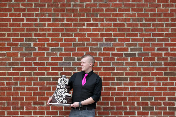 Owner Jason Hisley of Parkville holds a decorated cake sample outside of La Cakerie in Towson.