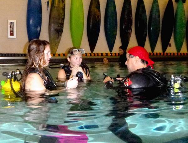 "Diveheart instructor Julio Garcia teaches scuba to Neuqua Valley ""peer partner"" students Tina Pawola, 16, (left) and Katrina Gerber, 17 who in turn helped students with special needs enjoy the water."