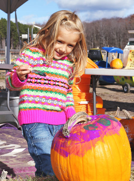 Emma Spencer, 4, of Harbor Springs, splashes her pumpkin with color in a creative moment during the harvest festival recently at Pond Hill Farm in Harbor Springs.