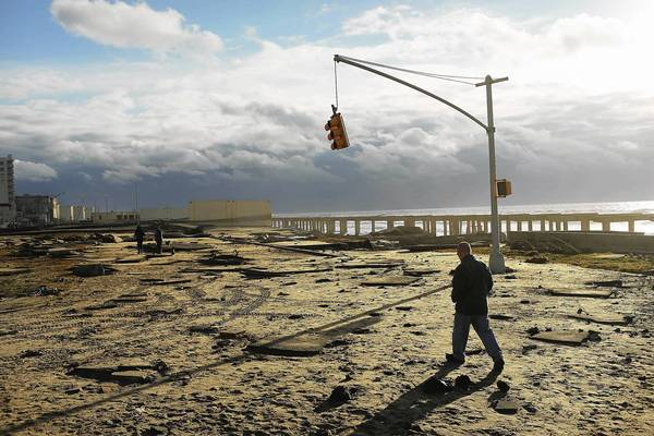 Photos: Hurricane Sandy: A man walks by the remains of part of the historic Rockaway boardwalk after large parts of it were washed away during Hurricane Sandy in the Brooklyn borough of New York City.