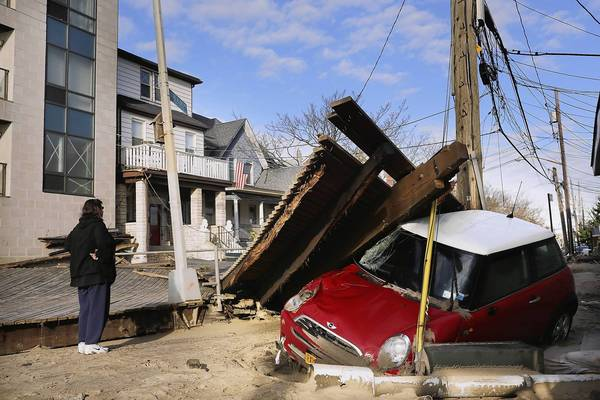 A woman looks at damage in the Rockaway neighborhood where the historic boardwalk was washed away during Hurricane Sandy in the Brooklyn borough of New York City.