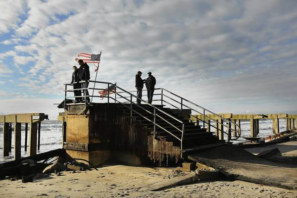 Residents stand on the remains of part of the historic Rockaway boardwalk after large parts of it were washed away during Hurricane Sandy in the Brooklyn borough of New York City.