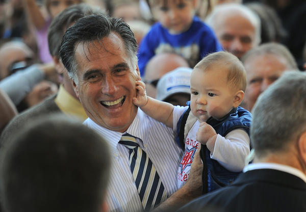Mitt Romney holds a supporter's baby during a rally at Landmark Aviation in Tampa, Fla.