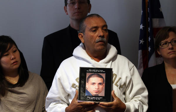 "Pascual Nunez holds a picture of his stepson Harry ""DJ"" Rodriguez, 23, who was killed by gunfire Oct. 23, 2011 in the Belmont-Cragin neighborhood. Cook County Board President Toni Preckwinkle today announced a $25 tax on firearms and a $2 million fund to combat gun violence with prevention programs."