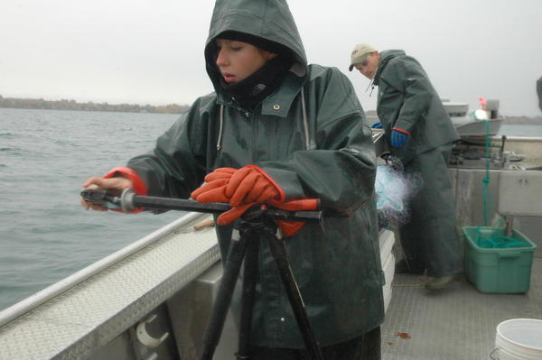 Laura Mathews, a graduate student at Central Michigan University, sets a camera up to take precise photos of netted lake trout before they are tagged and released back into Elk Lake.