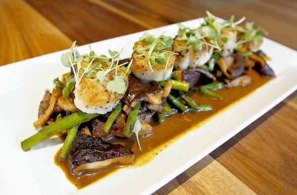 Wasabi pepper seared scallops on a bed of forest mushrooms and asparagus saute at the Back Bay Tavern in Whole Foods Market in Newport Beach.