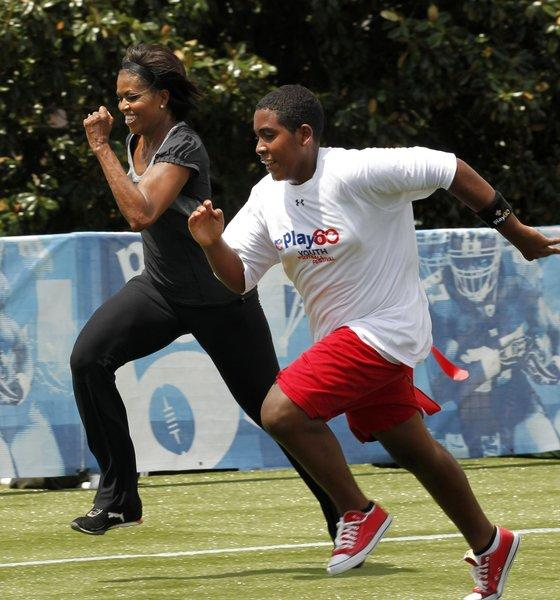 First Lady Michelle Obama runs with a student as part of an event for her campaign to get children to be more active.