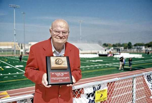 Vernon Ross, 76, a graduate of Burroughs Winter Class of 1955, has only missed three Burbank-Burroughs games. He is shown here at the Memorial Field dedication in February with a plaque displaying a block of wood from the original stadium bleachers.