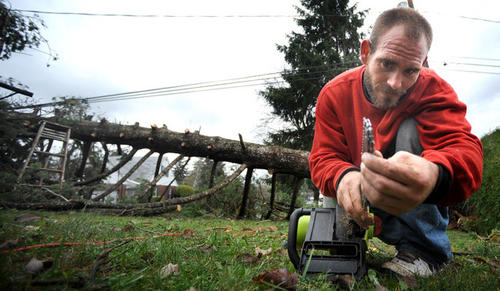 Charles Nonnemacher of Bethlehem prepares his saw as he gets ready to cut up a large pine tree that fell on his mother's Emmaus property Monday night at Glenwood Street at Mountain Boulevard in Emmaus.