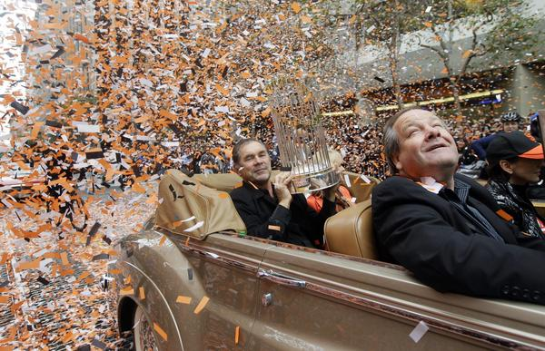 San Francisco Giants manager Bruce Bochy holds the World Series trophy as confetti falls during the  team's World Series victory parade.
