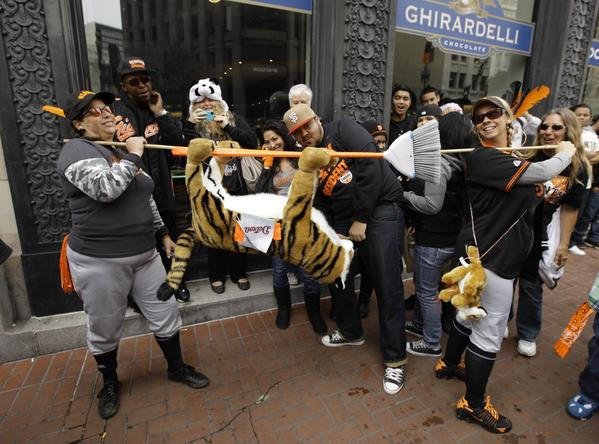 DeDe Krake, left, and Stacy Hunt of Auburn, Calif., carry a tiger on a broom while walking along Market Street before the start of the San Francisco Giants World Series victory parade.