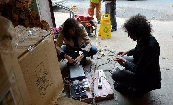 Two people try to charge their laptops and cellphones from a generator in New York.