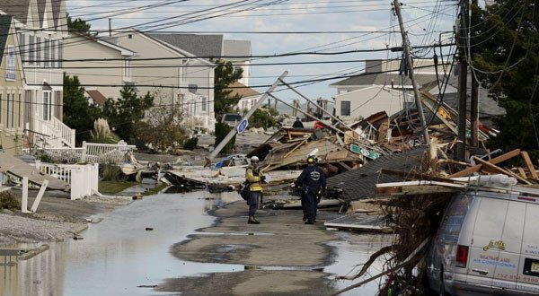 Emergency personnel in Seaside Heights, N.J., work on property and homes heavily damaged by Hurricane Sandy.
