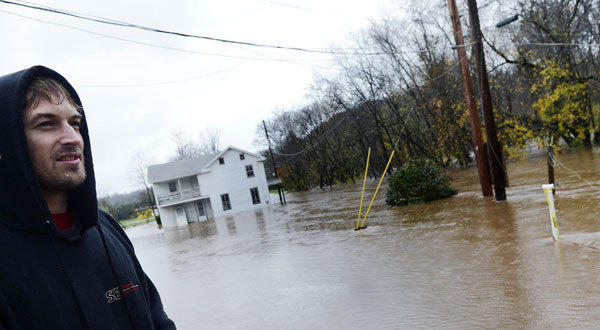 Jesse Lapp, general manager of a now flooded Halloween Park, stands in floodwater in Conewago Township, Pa.