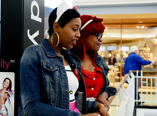 Dominique Campbell, left, and Erica Scott, dressed up for Halloween, look out over the rail at Towson Town Center mall Wednesday.
