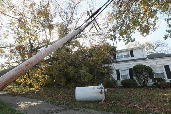 An electrical transformer and power lines rest in the yard of a house in the aftermath of Hurricane Sandy in Massapequa Park, N.Y.
