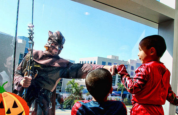 Edwin  William Motino, 4, watches as his brother Edwin, 3, bumps fists with the Night Owl, Matt Post, as super heroes wash the windows at the Joe DiMaggio Children¿s Hospital during their Happy Halloween Community Open House on Wednesday, October 31, 2012.