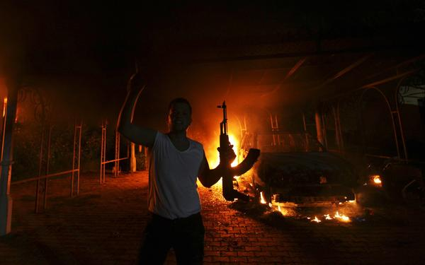 A protester reacts as the U.S. consulate in Benghazi is seen in flames on Sept. 11.