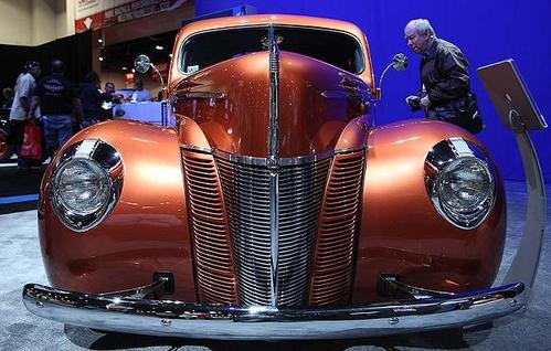 """A man looks inside the 1940 """"Catch Me If You Can!"""" Ford coupe."""