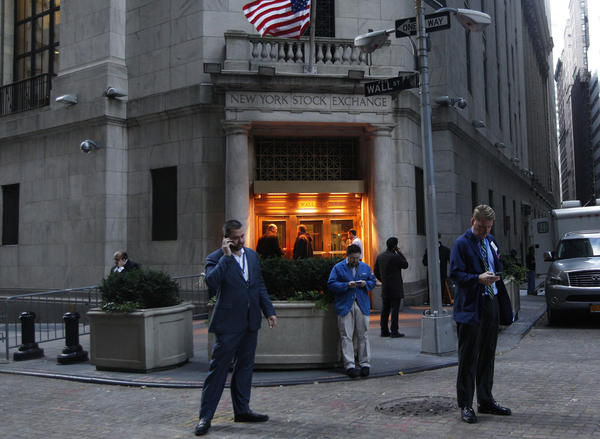 Traders stand outside the New York Stock Exchange prior to the opening bell. Monday and Tuesday's market closures marked the first two-day shutdown of the stock markets since a blizzard shuttered doors in 1888.