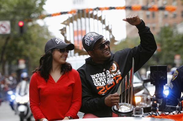 San Francisco Giants third baseman Pablo Sandoval reacts as he carries his most valuable trophy and is joined by his wife, Yoletzade, during the Giants' World Series winners parade along Market Street in San Francisco.