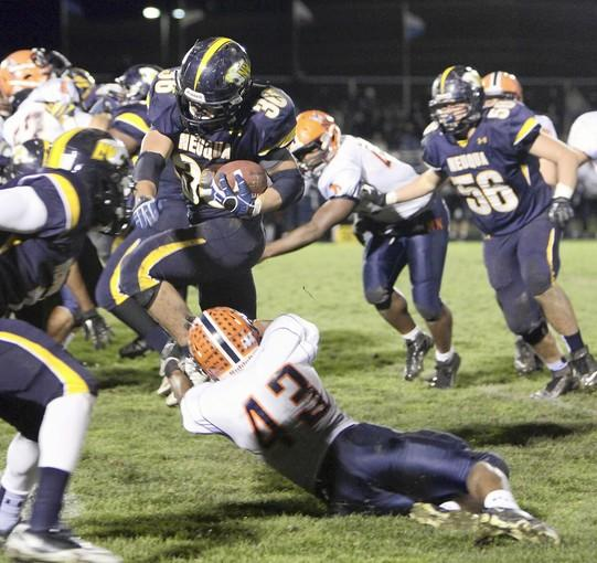 Neuqua Valley's Joey Rhattigan slips past Naperville North's Desean Brown at the Class 8A football playoffs at Neuqua Valley Friday, Oct. 26, 2012, in Naperville, Ill