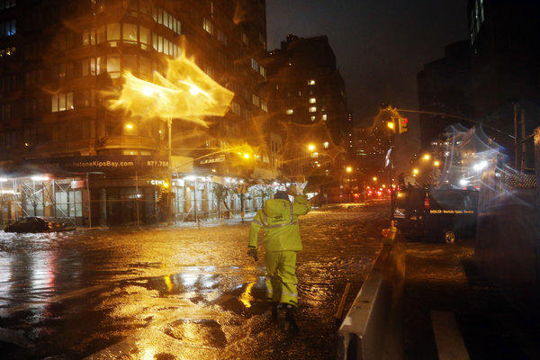 A Con Edison worker navigates the floodwaters in front of NYU Langone Medical Center in Manhattan during rains from Hurricane Sandy in New York City.