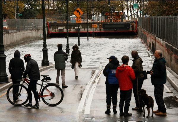New Yorkers are seen around the flooded Battery Park underpass after Hurricane Sandy.