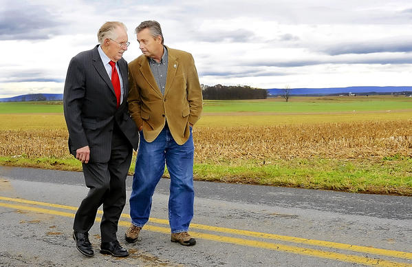 U.S. Rep Roscoe Bartlett, R-Md., left, and Washington County Board of Commissioners President Terry Baker talk as they walk along Hicksville Road Wednesday inspecting homes damaged by the storm.