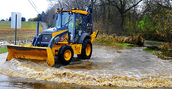Washington County highway worker Mark Trumpower maneuvers his backhoe Wednesday to help drain water from the flooded Leiters Mill Road.