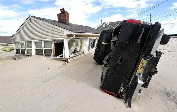 Sand from the beach reaches the windows of a home as a vehicle rests on its side in Seaside Heights, N.J.