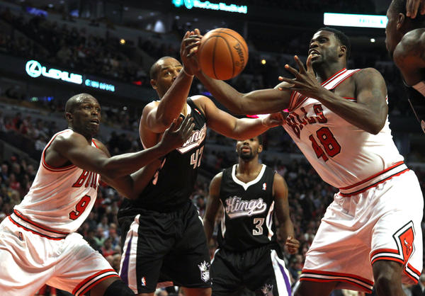 Kings' Chuck Hayes defends against Nazr Mohammed and Luol Deng during the first half.