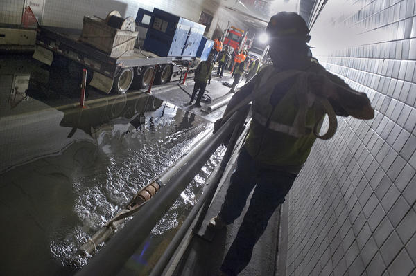 Employees from New York's Metropolitan Transportation Authority pump water out of the Brooklyn-Battery Tunnel.