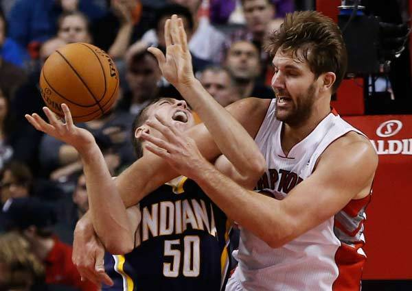 Toronto Raptors Aaron Gray battles for the ball with Indiana Pacers Tyler Hansbrough (L) during the second half of their game in Toronto.