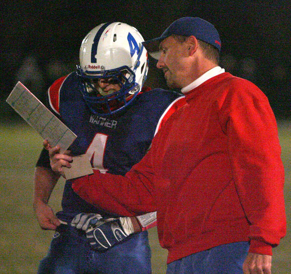 Warner football coach Tom Kulesa looks over a play with his quarterback Clay Rozell during a playoff game Monday night in Warner. Kulesa obtained his 100th career coaching victory during that contest.