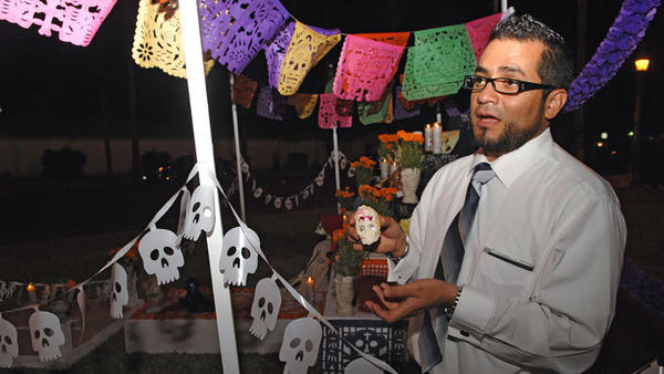 Martin Medina, Mexican Consulate education program coordinator, holds a skull made of sugar as he explains the symbolic meaning of items displayed on an altar for the dead during a Dia de los Muertos celebration at the consulate in Calexico last year.