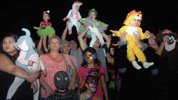 Parents lift their children for judges' viewing in the 0- to 5-year-old costume category contest during the Calexico Business Improvement District Halloween Carnival in downtown Calexico on Wednesday. Ana Paula Miranda, 3, wearing a Cinderella costume, won first place.