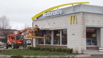 Workers tend to some exterior details Wednesday at the newly rebuilt McDonald's restaurant in Petoskey.
