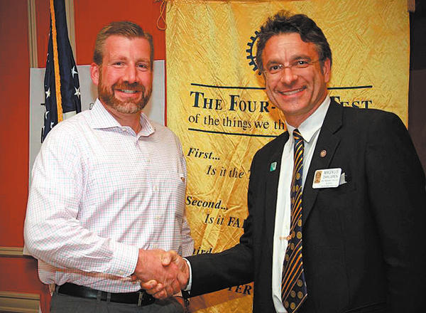 Magnus Dahlgren, right, congratulates Justin Harbert on becoming a member of the Rotary Club of Long Meadows.
