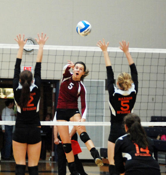 Charlevoix sophomore Madeline Boss (middle) spikes the ball against the block of Harbor Springs' Tori Allore (left) and senior Katie Barkley during Wednesday's Class C district semifinal match at the Boyne City High School gym.