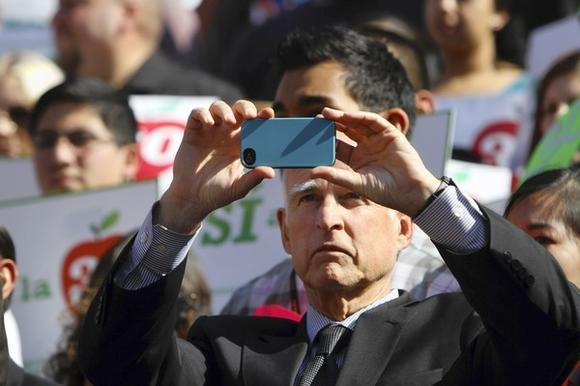 Gov. Jerry Brown takes a photo of the crowd at Cal State Los Angeles during a rally to support Proposition 30, Brown's tax initiative.
