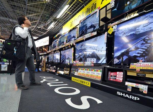 A customer checks LCD television sets by Sharp, which said it will book a record $5.6 billion annual net loss.