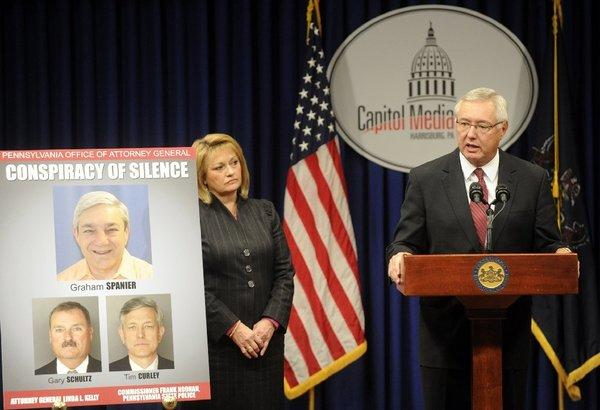 Pennsylvania Attorney General Linda Kelly's office displays a poster of Former Penn State President Graham Spanier, Timothy Curley and Gary Schultz during a news conference Thursday.