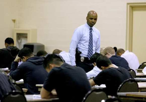 Glendale Police Detective Victor Jackson keeps an eye on applicants taking the police officer recruit written exam at the Glendale Civic Auditorium in Glendale on Thursday, Nov. 1, 2012.