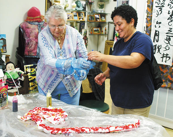 Mari Singing, left, and Melinda Freeman demostrate the tie-dye method on a T-shirt at Contemporary School of the Arts and Gallery Inc. at 4 West Franklin. St. in Hagerstown. For more information about classes offered at the gallery, call 301-791-6191, send an email to ronlytle3@netzero.net or go to csagi.org.
