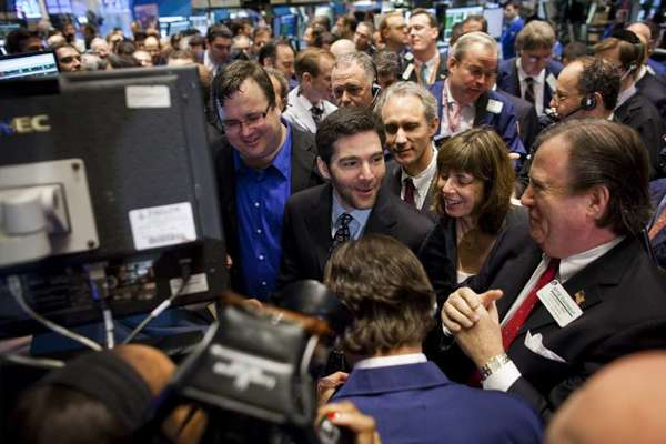 Reid Hoffman, co-founder and chairman of LinkedIn, left, and Chief Executive Jeffrey Weiner, center, stand with traders on the floor of the New York Stock Exchange during the company's initial public offering of stock.
