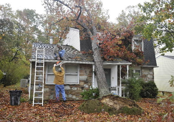 John Ball, on roof, gets help from John Cain as they look to trim a few branches from a tree that fell on a friend's house in the 400 block of S. Law St. in Aberdeen.
