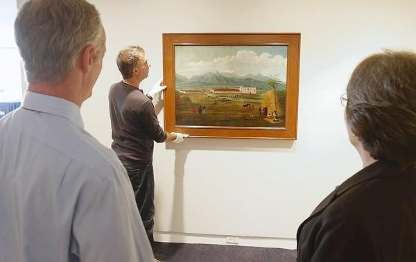 "Executive Director Malcolm Warner, left, and Janet Blake, curator of early California art, watch as the Ferdinand Deppe's ""San Gabriel Mission"" is hung at the Laguna Beach Museum of Art."